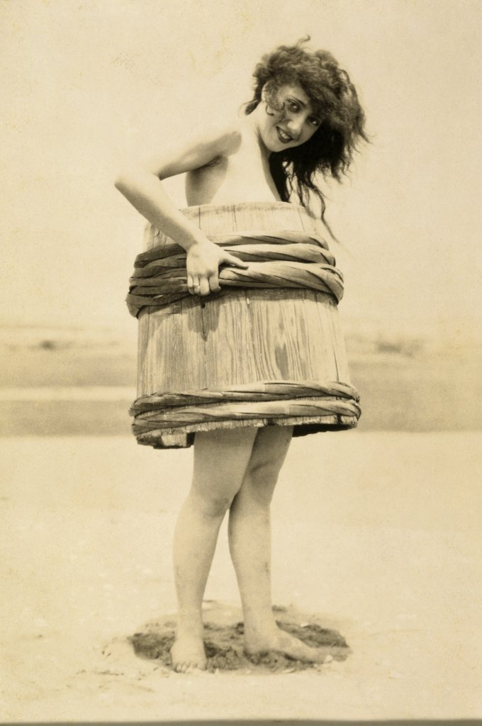 Portrait of a young woman covering her body with a barrel : Stock Photo