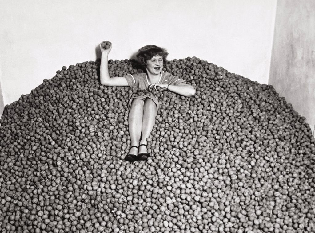 Stock Photo: 1035-997 Mid adult woman in a heap of walnuts