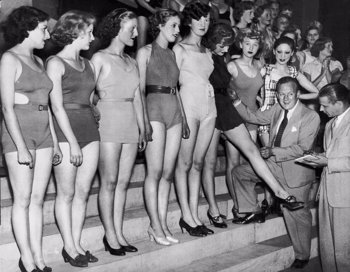 London, England:  August 28, 1935 Band leader Jack Hylton, assisted by American impresario  Howard Deighton, is selecting a hundred bathing beauties to appear with him in his first film which is now in production at  Twickenham Studios. Here he is measuring one of the women.  - stock photo
