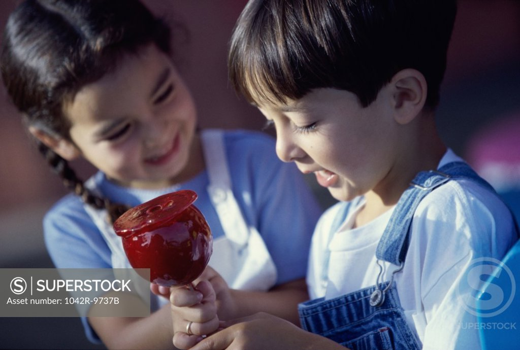 Stock Photo: 1042R-9737B Girl and a boy sitting together holding a candy apple