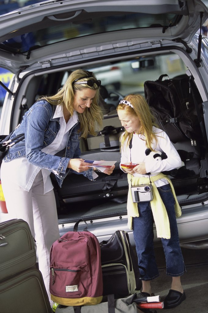 Mother and her daughter standing at the back of a car : Stock Photo
