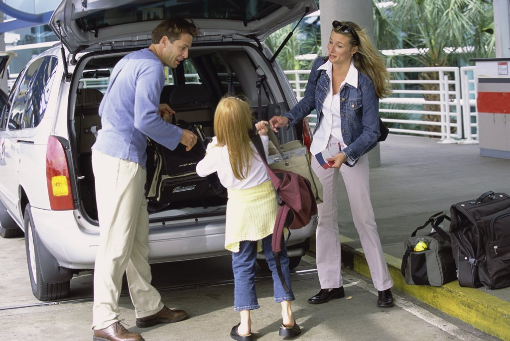 Parents with their daughter standing at the back of a car : Stock Photo