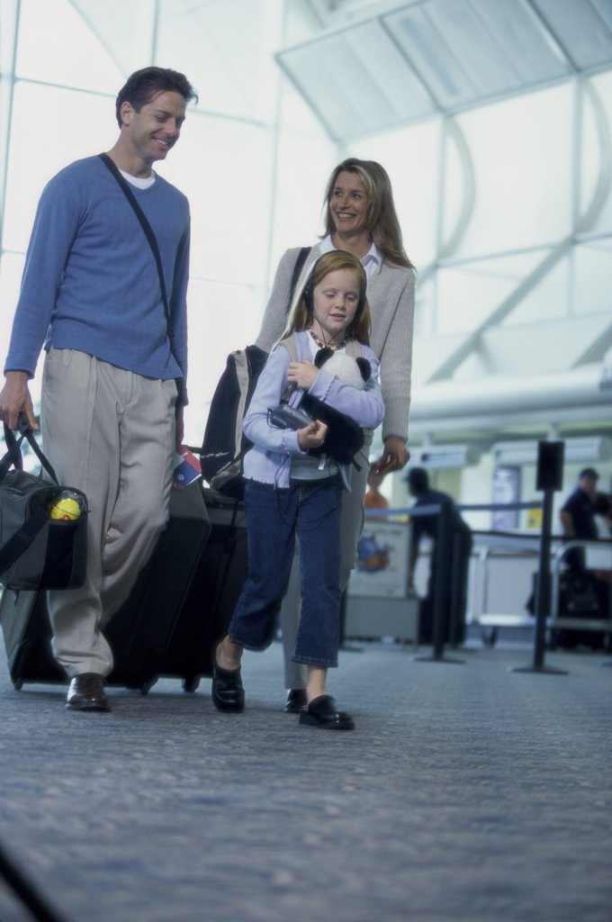 Low angle view of parents with their daughter walking in an airport : Stock Photo