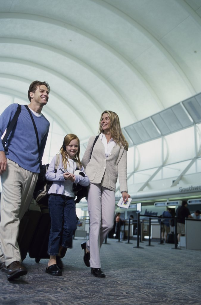 Stock Photo: 1042-10278B Low angle view of parents with their daughter walking in an airport
