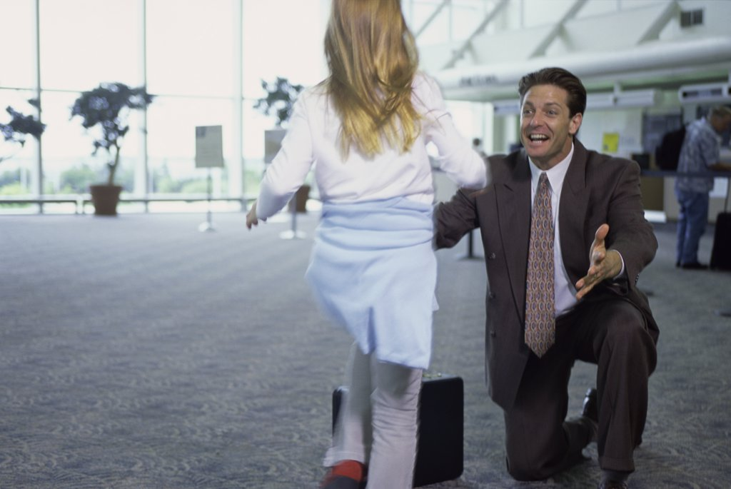 Father greeting his daughter in an airport : Stock Photo