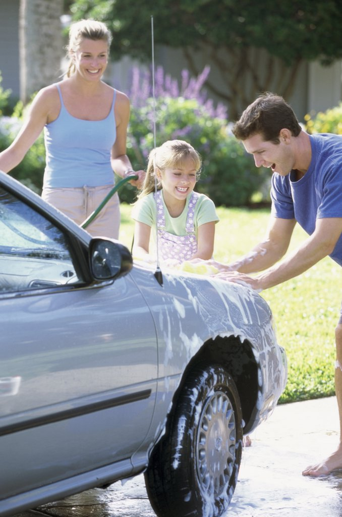 Parents washing the car with their daughter : Stock Photo