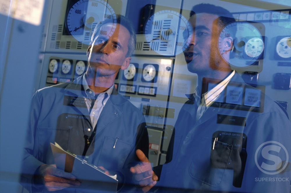 Reflection of two mid adult men on a control panel : Stock Photo