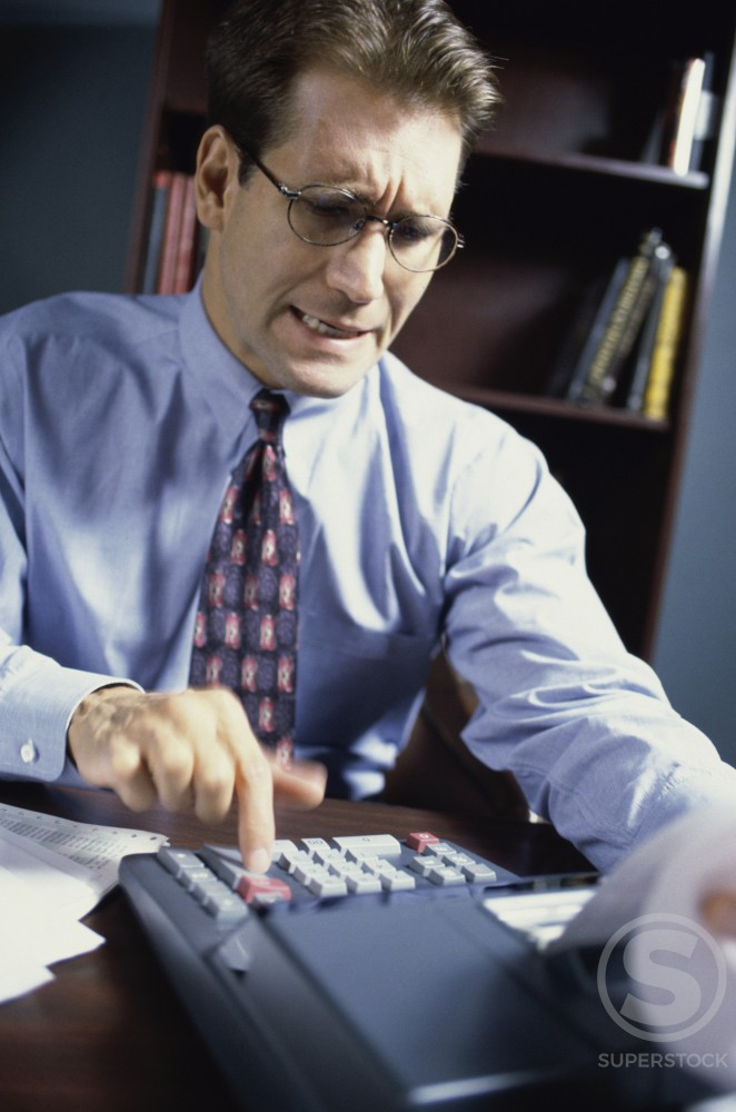 Businessman using an adding machine : Stock Photo