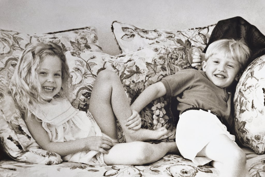 Stock Photo: 1042-2331 Portrait of a girl and a boy sitting on a couch