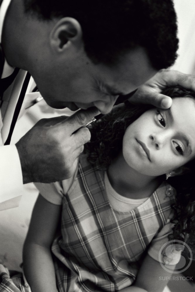 Stock Photo: 1042-2508 Male doctor examining a girl's eyes