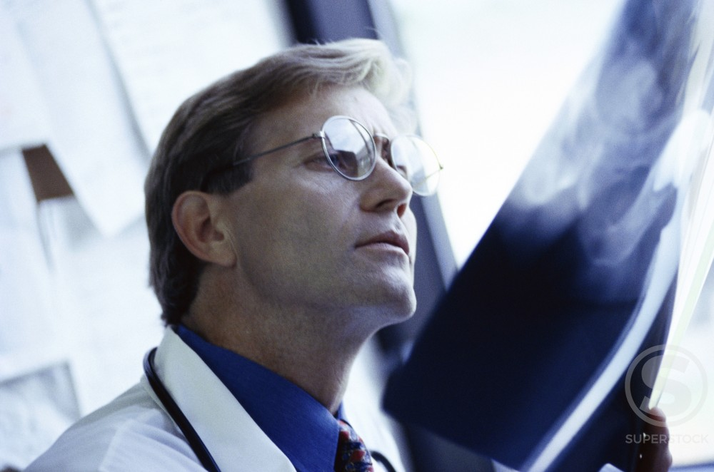 Side profile of a male doctor examining an x-ray report : Stock Photo