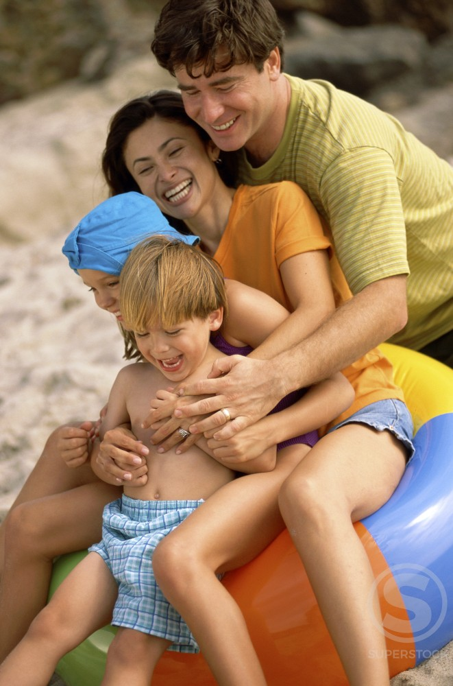Stock Photo: 1042-2837 Young couple playing with their son and daughter