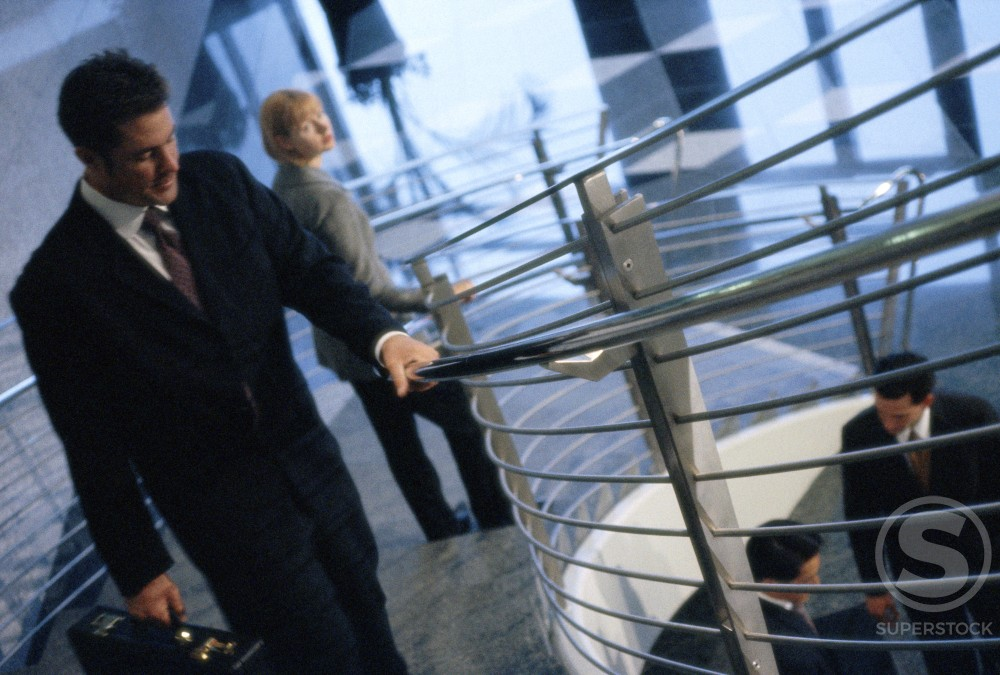 Businessman walking up a spiral staircase : Stock Photo