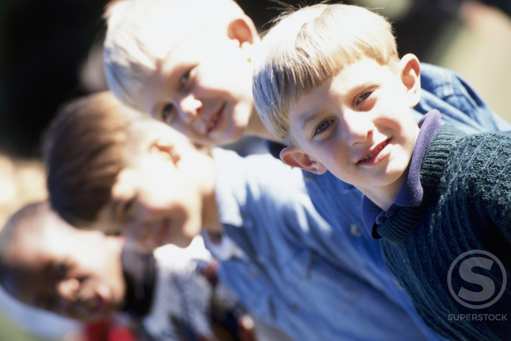 Side profile of four boys standing side by side : Stock Photo