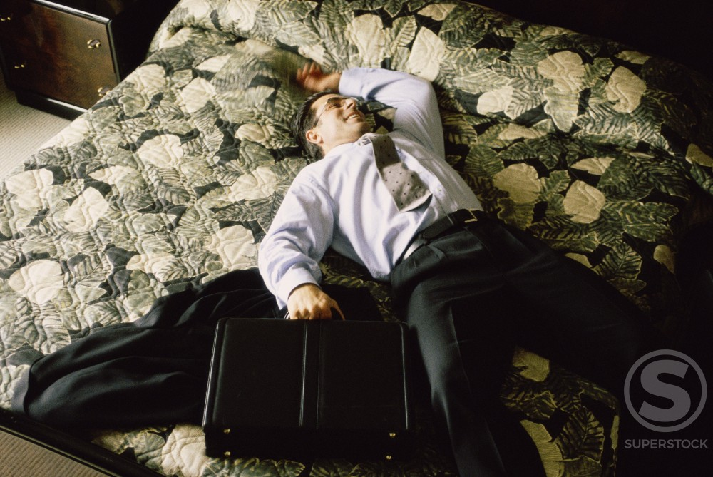Stock Photo: 1042-3673 Young businessman lying on a bed