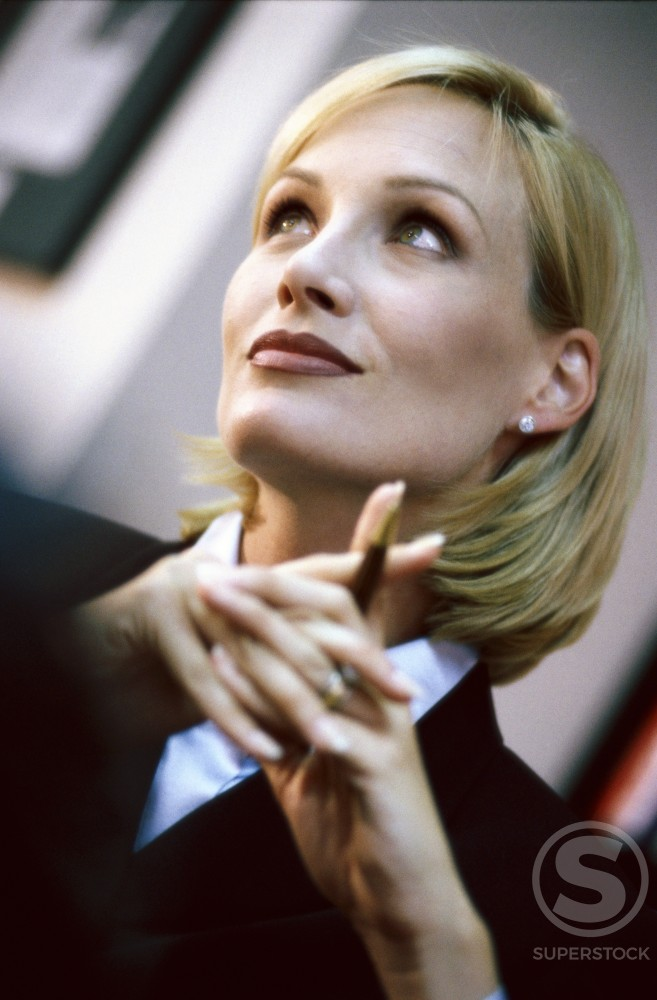 Stock Photo: 1042-3722 Low angle view of a businesswoman holding a pen
