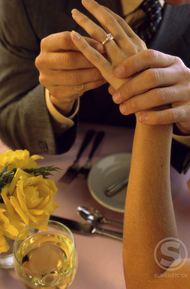 Man placing a wedding band on a woman's finger : Stock Photo