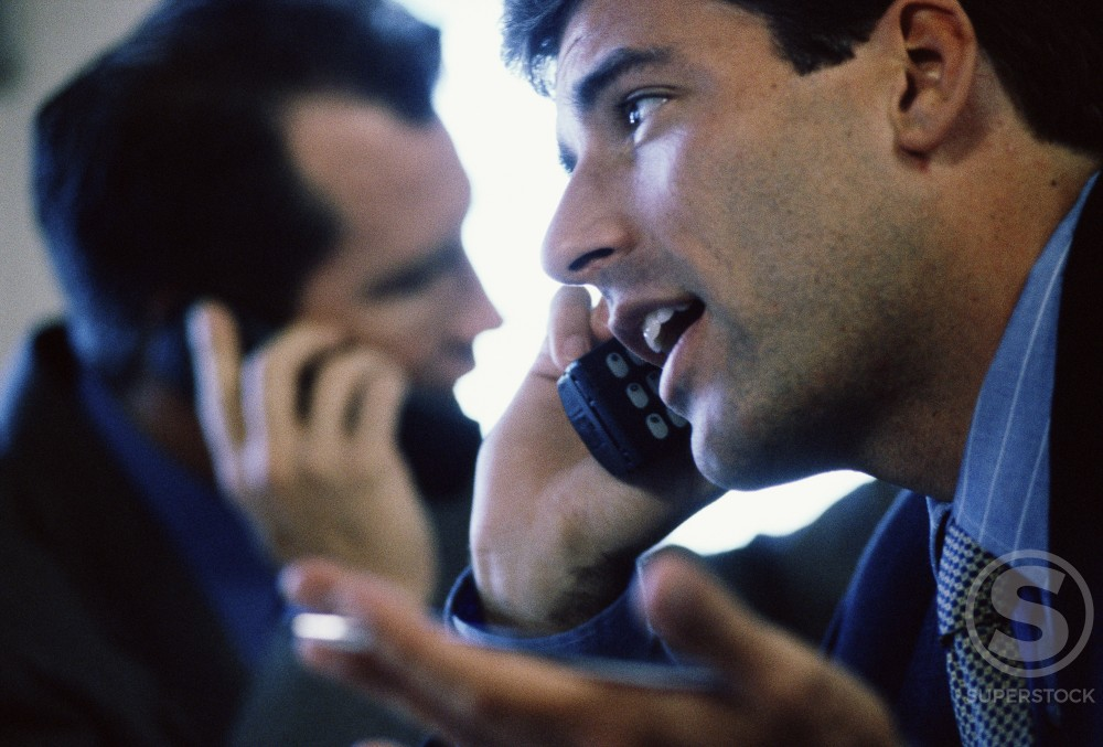 Stock Photo: 1042-3791A Two businessmen talking on mobile phones