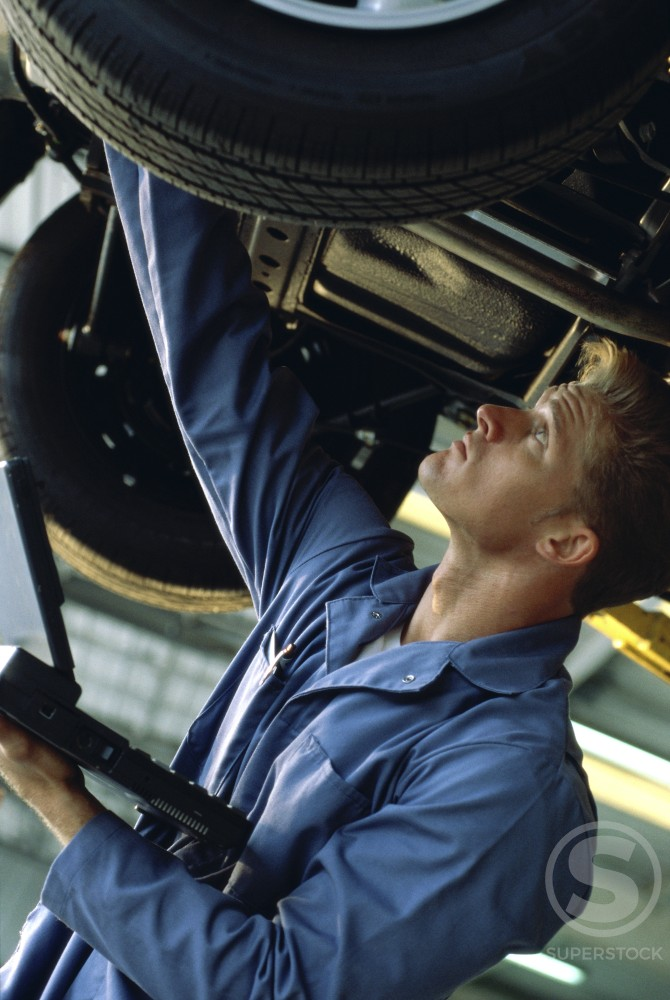 Side profile of a young man working under a raised car : Stock Photo