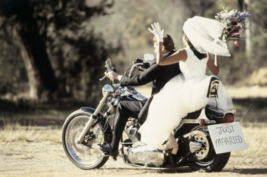 Rear view of a newlywed couple riding on a motorcycle : Stock Photo