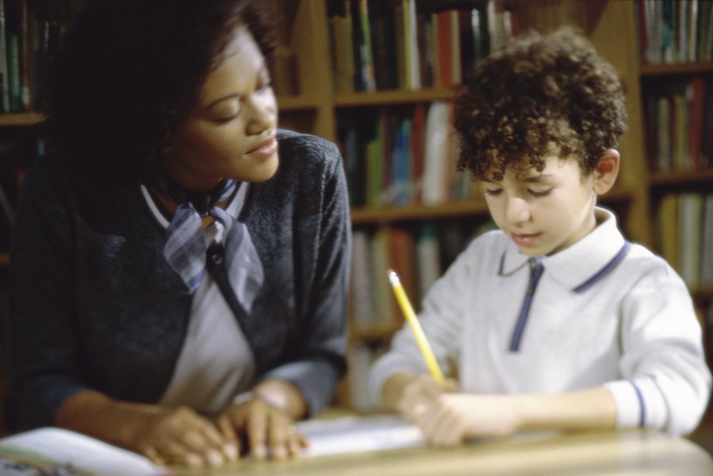 Teacher teaching a boy : Stock Photo
