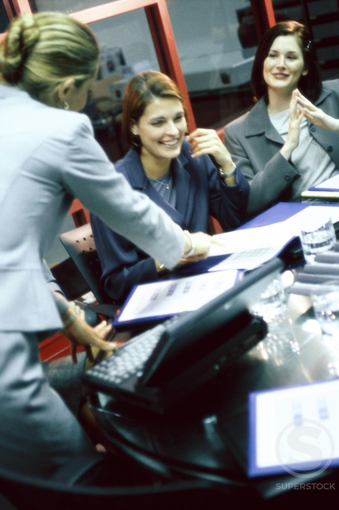 Stock Photo: 1042-4597 High angle view of three businesswomen talking in an office