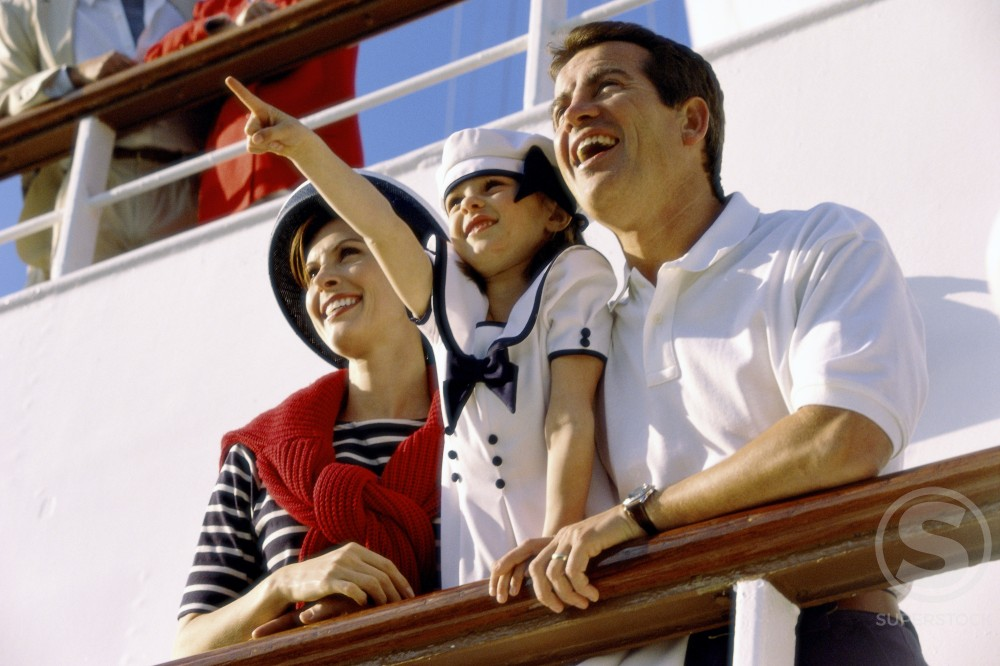 Low angle view of a young couple and their daughter standing on a cruise ship : Stock Photo