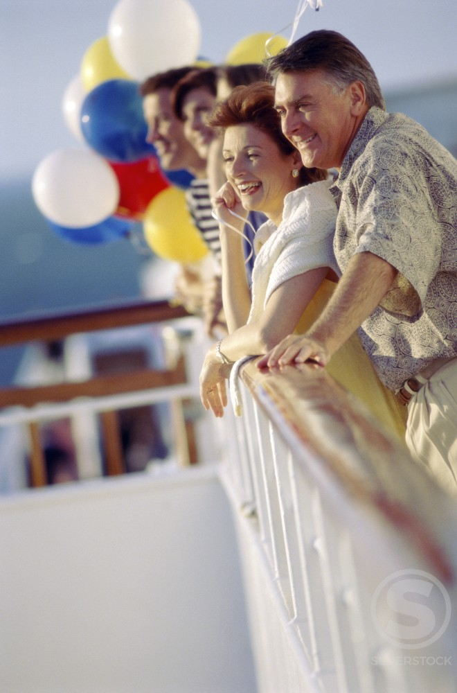 Side profile of a group of people standing on a cruise ship : Stock Photo