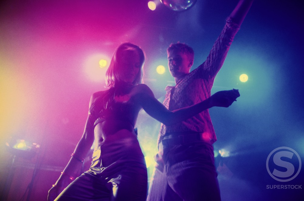 Stock Photo: 1042-5601 Low angle view of a teenage couple dancing at a nightclub