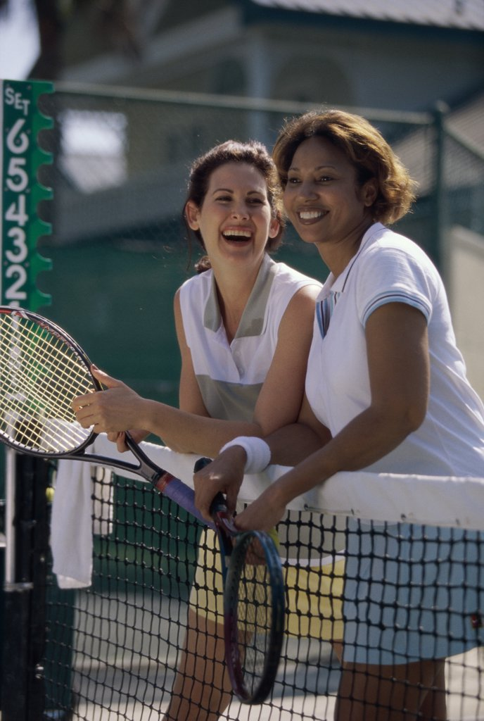 Two mid adult women standing against a tennis court net : Stock Photo