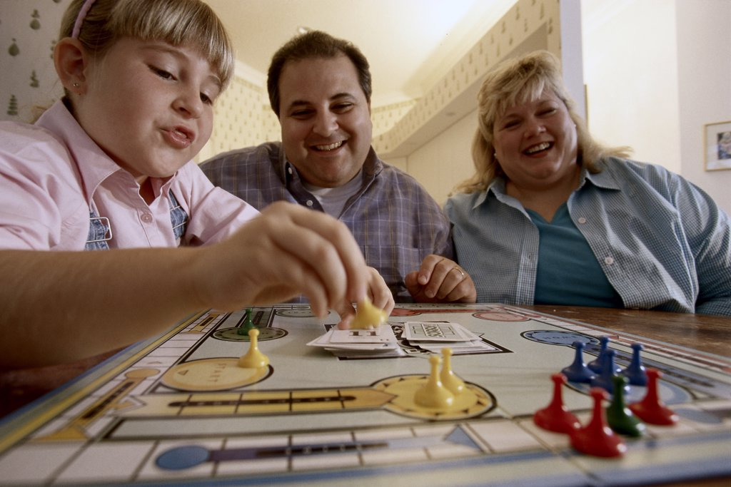 Parents and their daughter playing a board game : Stock Photo