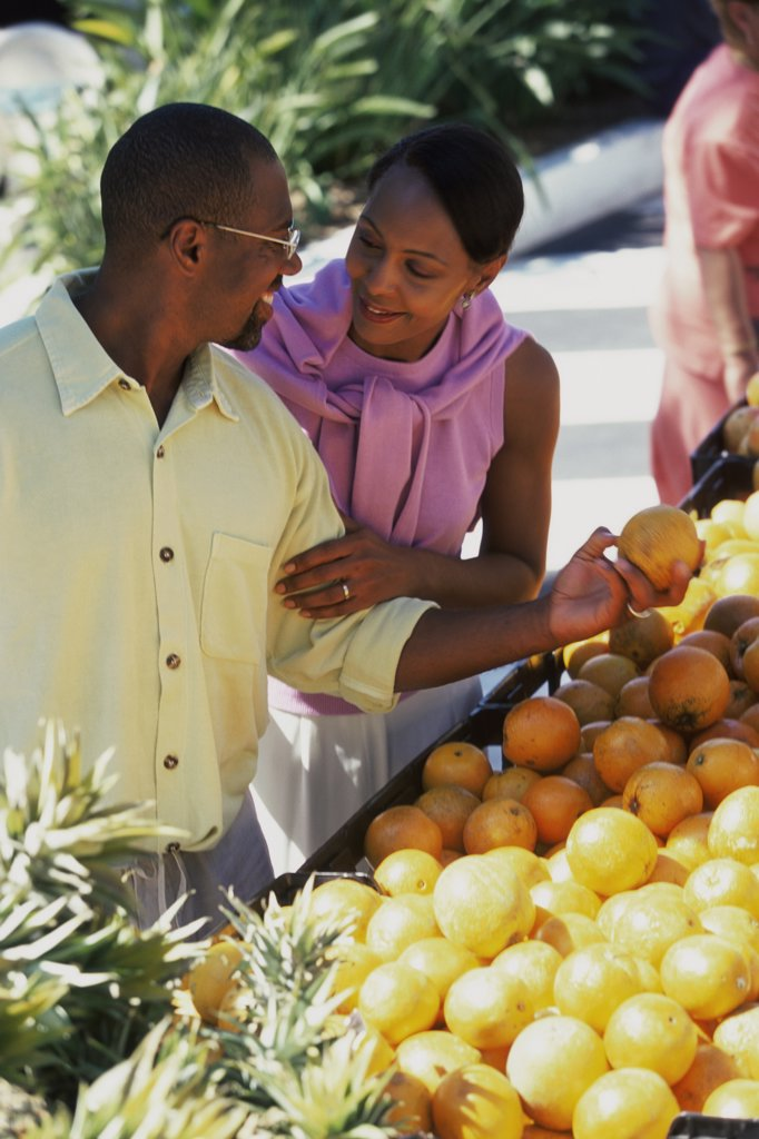 Mid adult couple choosing fruit at a fruit stand : Stock Photo