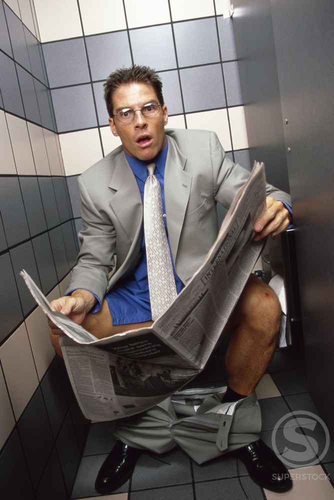 Businessman sitting on a toilet holding a newspaper : Stock Photo