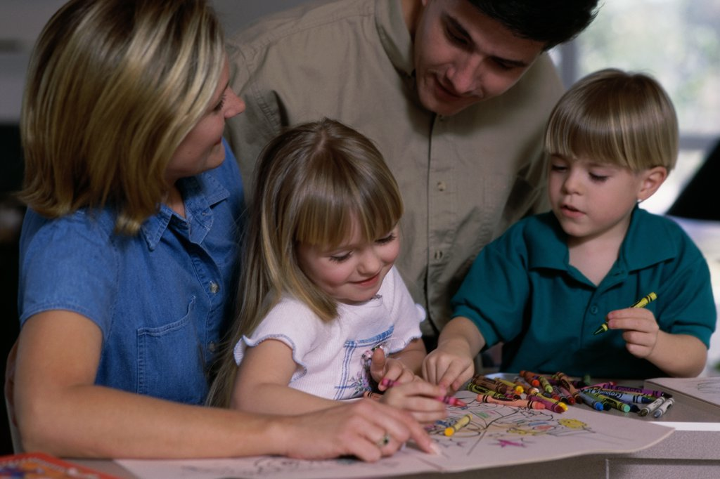Stock Photo: 1042-753 Parents helping their son and daughter to color using crayons
