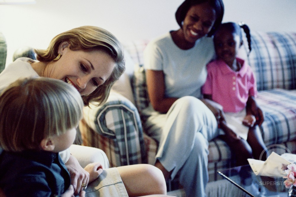 Two mothers sitting with their son and daughter on a couch : Stock Photo