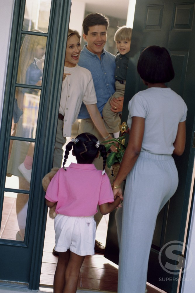 Rear view of a mother and her daughter greeting a family at the front door : Stock Photo