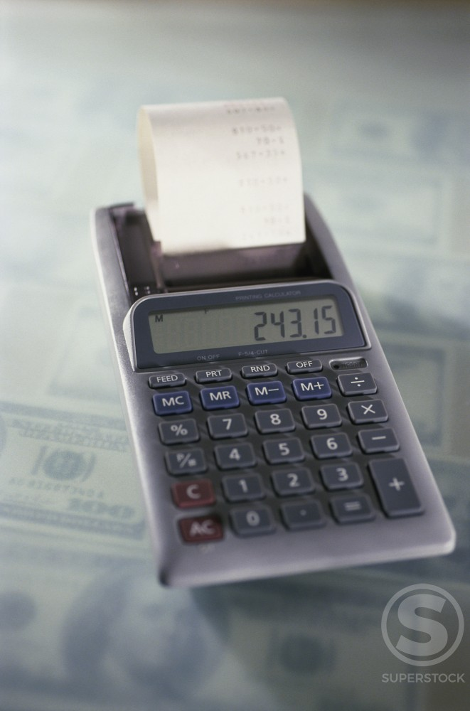 Calculator on American dollar bills : Stock Photo