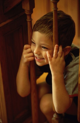 Boy peeking through a wooden banister : Stock Photo