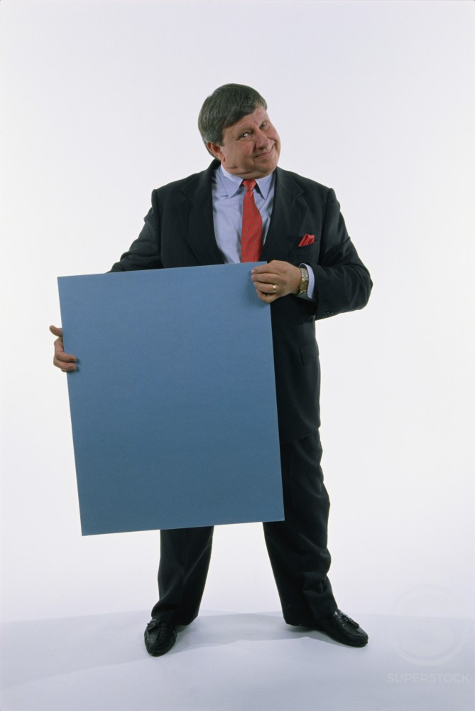 Portrait of a businessman holding a placard : Stock Photo