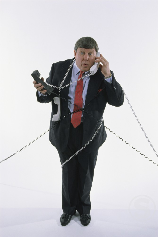 Stock Photo: 1042R-8233 Businessman holding landline telephone receivers
