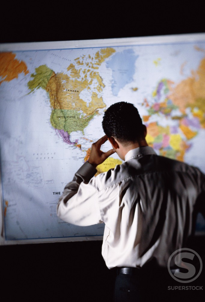 Stock Photo: 1042R-8340A Rear view of a businessman in front of a map