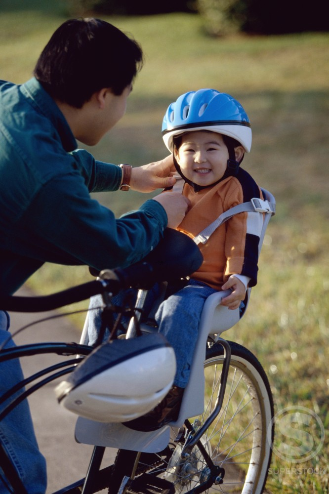 Stock Photo: 1042R-8907 Father fastening the strap of a cycling helmet on his daughter