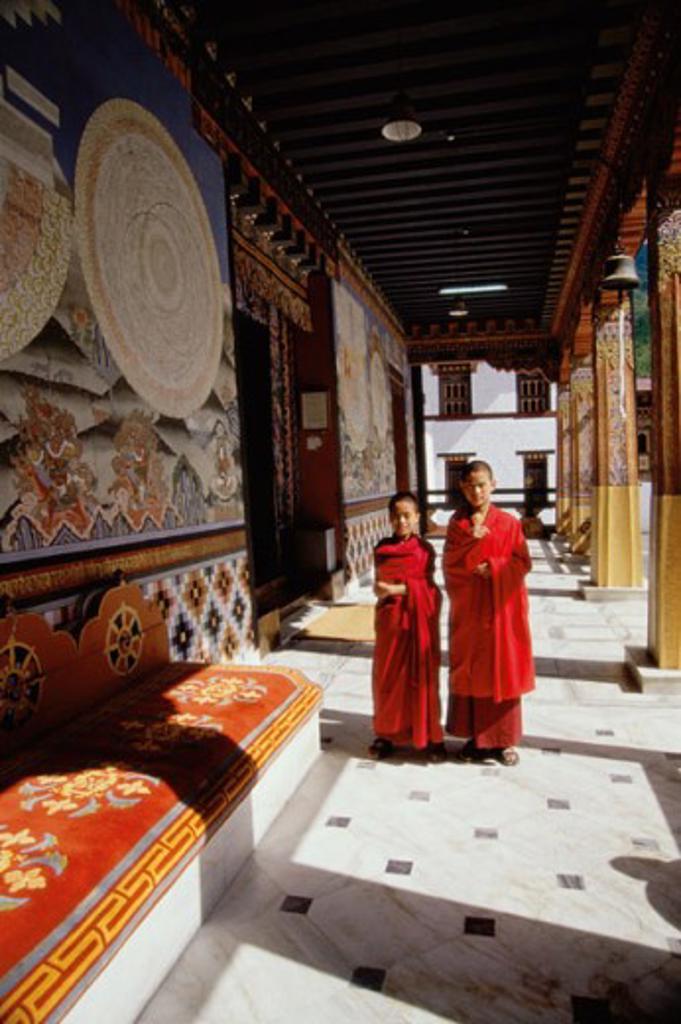 Two monks standing in a corridor of a temple, Trashi Chhoe Dzong, Thimphu, Bhutan : Stock Photo