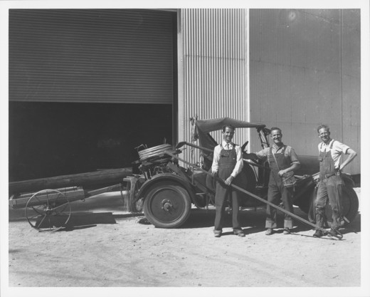 CAR WITH TRAILER CARRYING WOOD [TELEPHONE?] POLE IN FRONT OF 100-INCH TELESCOPE BUILDING WITH THREE MEN. : Stock Photo