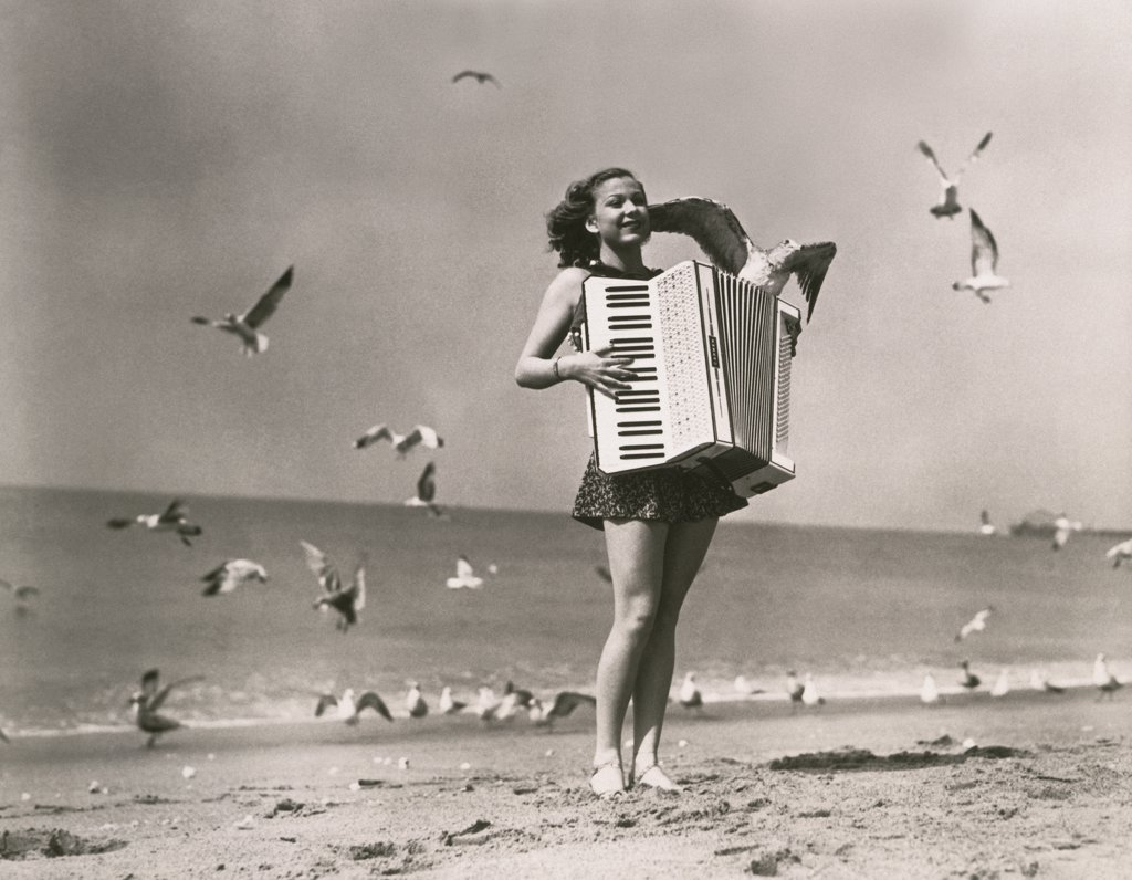 Woman playing the accordion on the beach : Stock Photo
