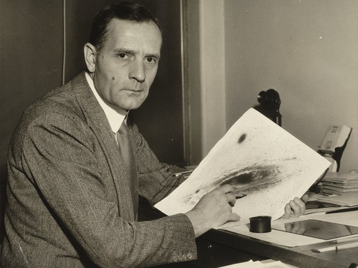 Edwin Powell Hubble at desk, holding photograph of galaxy and looking at camera : Stock Photo