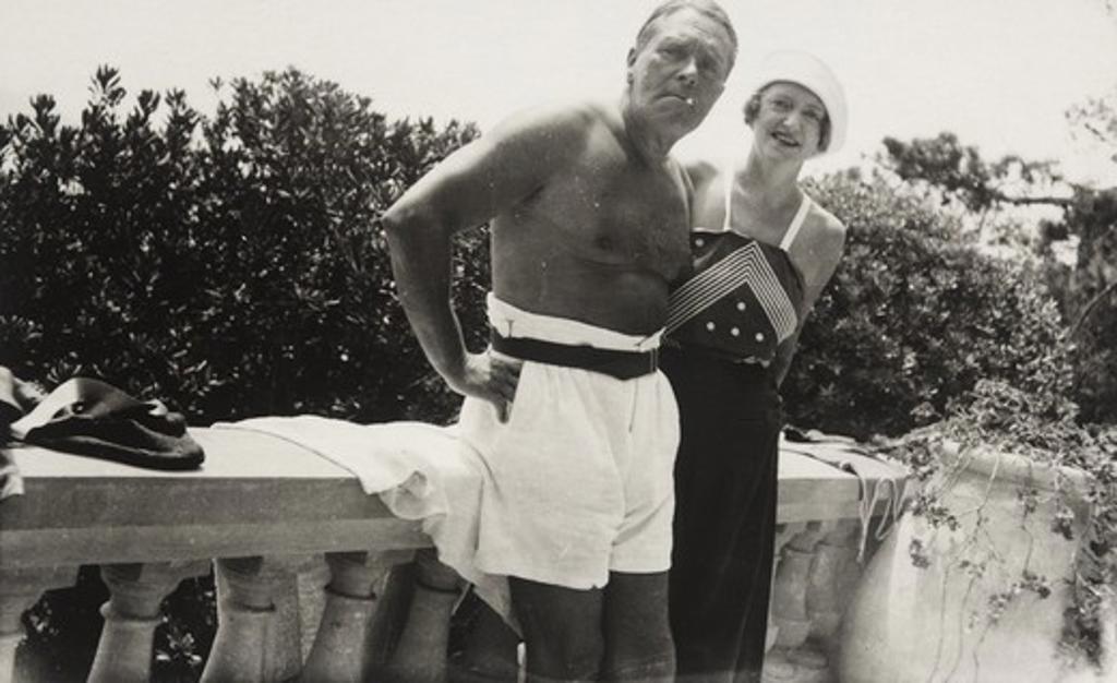 Harold Marsh Harwood and Fryniwyd Tennyson (Jesse) Harwood standing against cement railing : Stock Photo