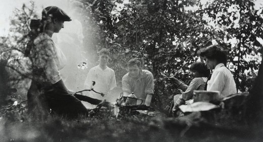 Edwin Powell Hubble (center) and unidentified companions (two women, one girl, and two adolescent boys) sitting around camp fire : Stock Photo