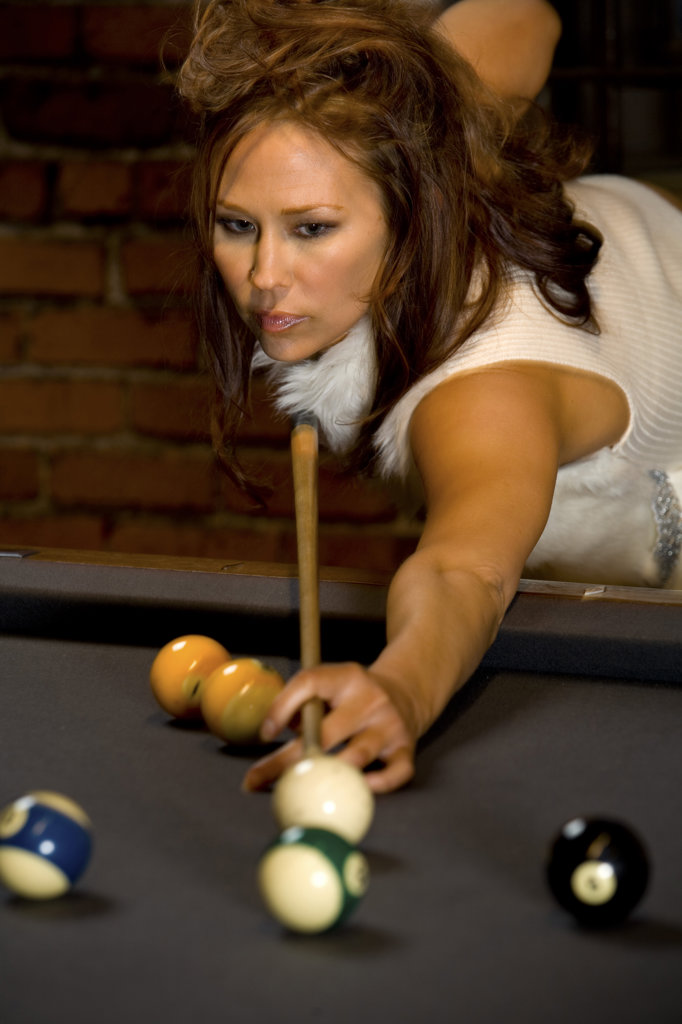 Young woman playing pool game : Stock Photo