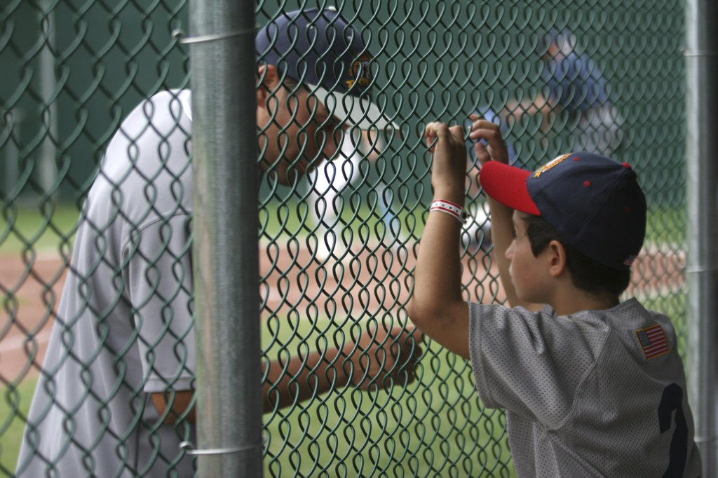 Boy discussing with a baseball player across a chainlink fence : Stock Photo